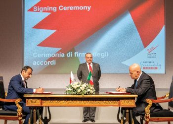 Shaikh Mohammed and Descalzi sign the agreement as HRH the Crown Prince looks on